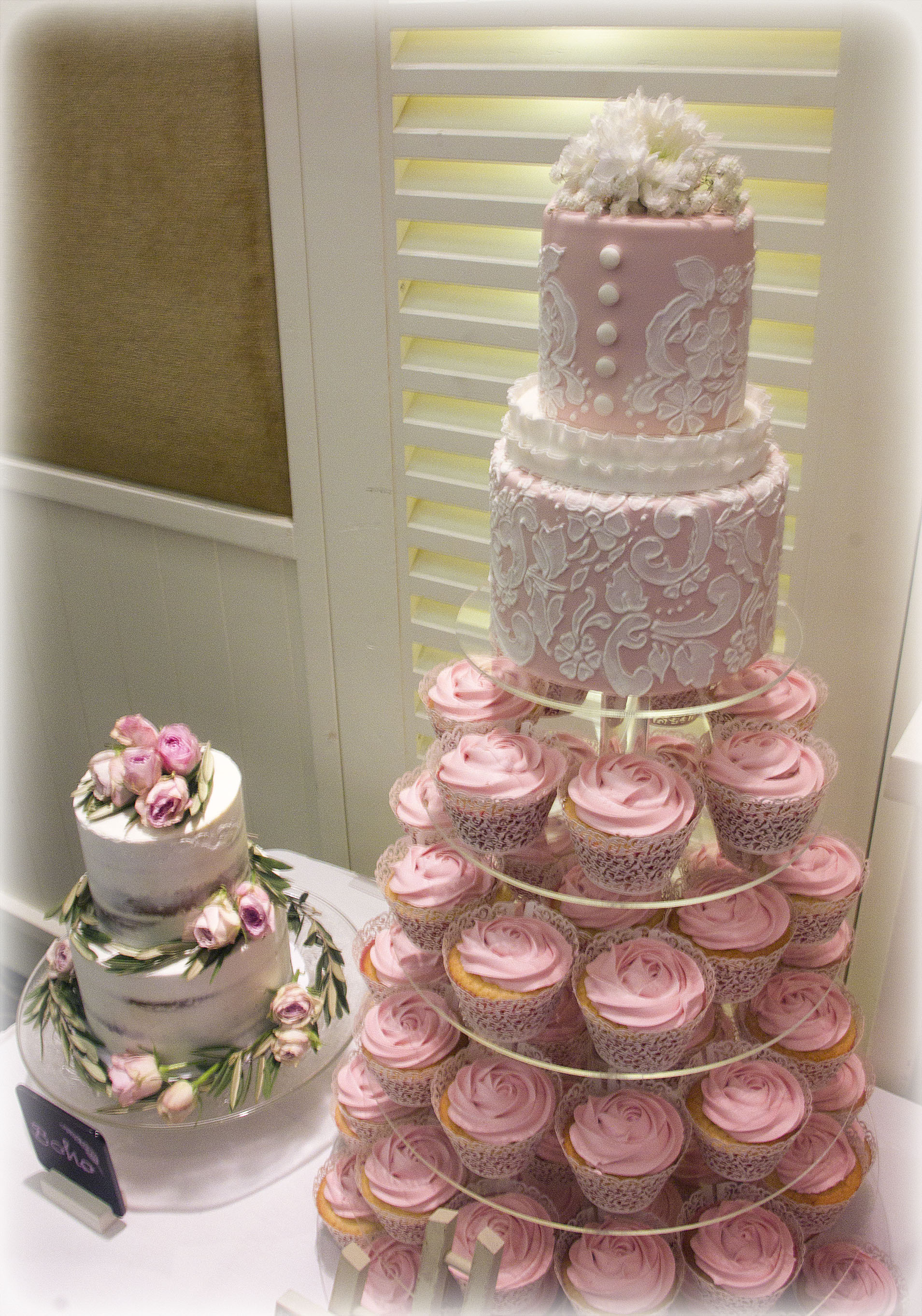 Pink Lace two tier wedding cake with pink swirl cupcakes on a 5 tier cake/cupcake acrylic stand.